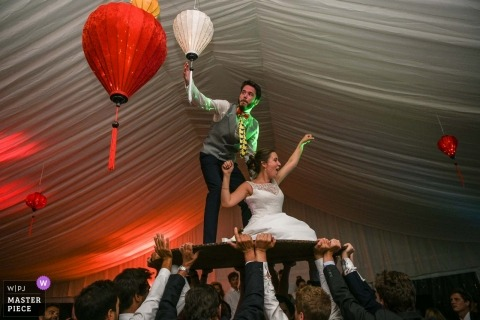 Nouvelle-Aquitaine wedding shot with a couple lifted up on round table on the reception dance floor