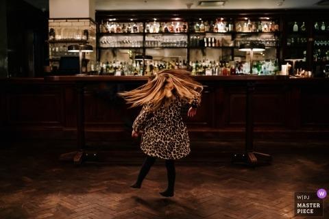 London documentary wedding photo of little girl dancing near bar