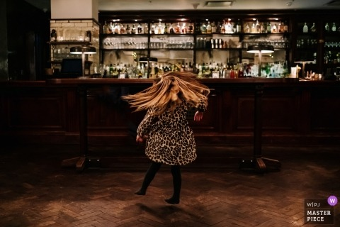 London documentary wedding photo of little girl dancing near bar