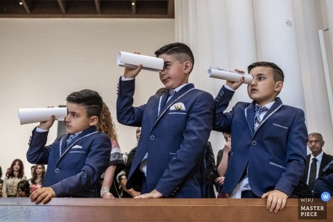 Wedding photo of boys at ceremony with paper scopes in Reggio Calabria