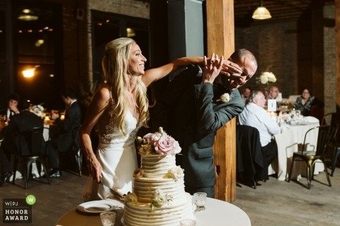 Artifact Events Chicago | Picture of a couple smashing cake by a top Chicago wedding photographer