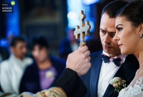 Plovdiv, Bulgarie photojournalisme de mariage image d'un couple et de la croix lors de la cérémonie de l'église