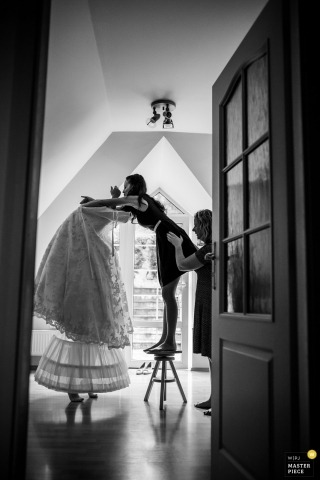 Prague documentary wedding photo of bridesmaid standing on stool helping bride into dress
