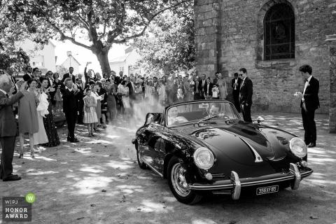 Domaine de la Bretesche婚禮照片的夫婦離開老式可轉換汽車| 婚紗攝影