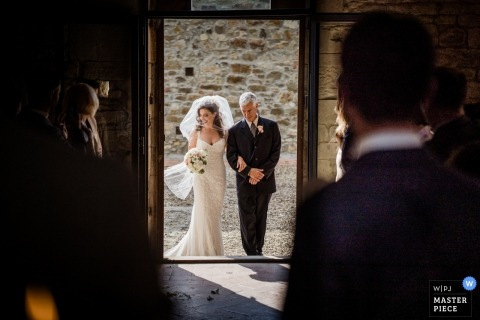 Photo of the bride and her father entering the Florence, Tuscany church for the wedding.