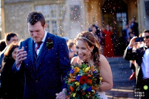 Horsley Towers, Surrey, England | wedding photojournalism image of a couple with wedding confetti emotions