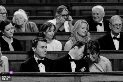 Wedding photojournalism at Trinity Chapel, Dublin, Ireland of emotional guests in the pews