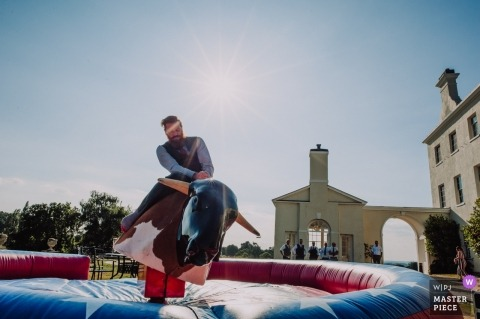 Devon documentary wedding photography of a man writing a mechanical bull outside in the sun
