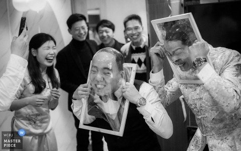 Linwei District of Weinan City, Shaanxi Province, the groom and groomsman are playing games with their relatives. They need to break the plastic film with their faces. The plastic film deforms the face and makes the scene laugh co