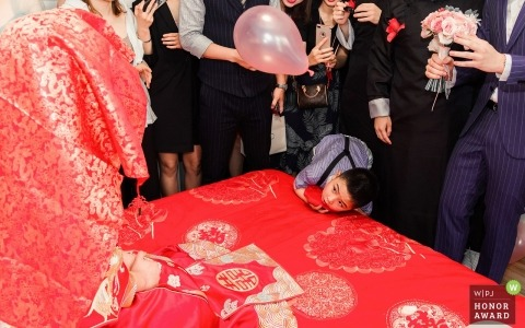 Documentary wedding photography at  Weinan City, Shaanxi Province, China - a naughty child looks curiously at the bride under the hood