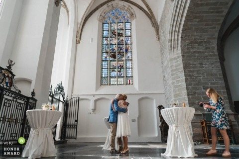 Zuid Holland wedding photojournalism image of guests hugging inside the church