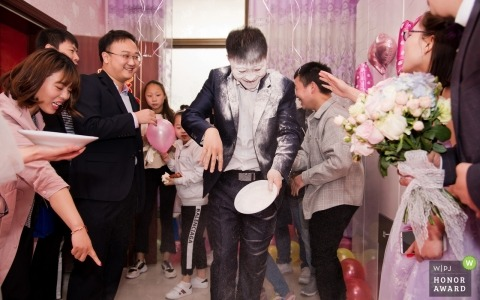 Weinan City, Shaanxi Province, China, during the greeting game, the best man tried to find candy with his tongue in the flour on the plate. As a result, a friend next to him touched the plate and spilled the best man's face