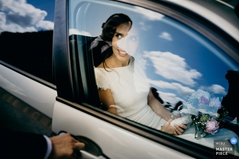 Porto wedding photo of the groom opening the door as the sky and clouds are reflected in the window glass