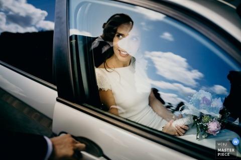 Porto photo de mariage du marié ouvrant la porte alors que le ciel et les nuages se reflètent dans la vitre