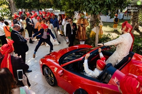 Waldorf Astoria Dubai wedding photo | wedding photograph of the groom arriving in a red convertible Ferrari as men dance before the car