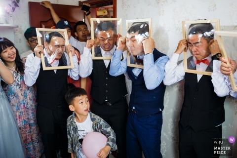 Shandong-Hochzeitsfotografie von uns kleinem Jungen, der einen rosafarbenen Ballon verwirrt hält, während er die chinesischen Türspiele aufpasst