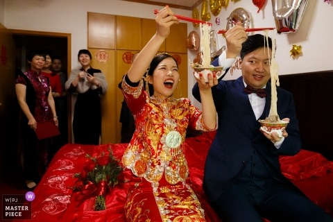 Shandong wedding photojournalism image of a couple enjoying a noodles together with chopsticks on the bed