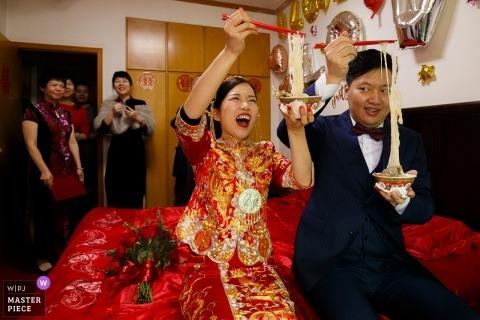 Shandong bruiloft fotojournalistiek beeld van een paar genieten van een noedels samen met stokjes op het bed