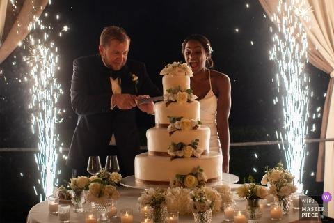 Villa Foscarini Rossi Padova huwelijksshoot met een paar dat 's avonds buiten haar cake snijdt met vuurwerkdouches