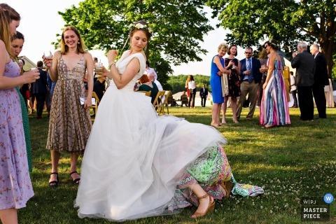 Huwelijksfoto's door Maine fotograaf van een bruid die hulp krijgt bij het bedruipen van haar jurk terwijl gasten zich mengen op het gras onder schaduwrijke bomen bij haar receptie