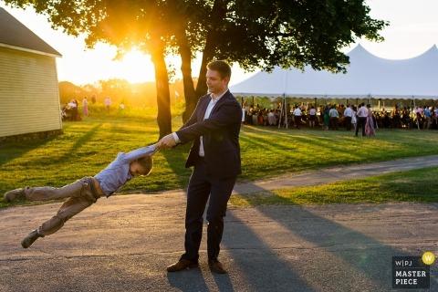 Maine-Hochzeitsfotografie eines Gastes, der seinen kleinen Jungen durch die Arme bei Sonnenuntergang nahe der zeltierten Aufnahme schwingt
