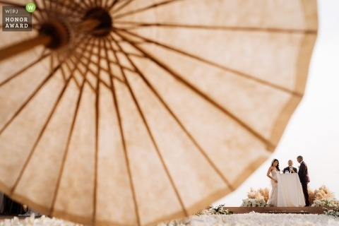 Phuket wedding shoot with a couple and umbrellas for the sun at the outdoor ceremony