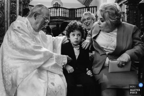 Ouro Preto dokumentarisches Hochzeitsfoto des Priesters, der mit einem Jungen in der Kirche spricht