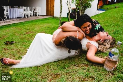 Het huwelijksfoto van São Paulo van een bruid die op het gras legt dat een alcoholische drankfles met vrienden bovenop haar houdt Brazilië huwelijksfotografie