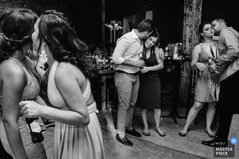 Wedding photo of three couples dancing at the reception with beer bottles in Tiradentes