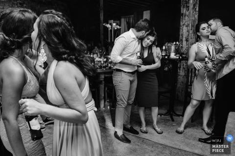 Huwelijksfoto van drie paren die bij de ontvangst met bierflessen dansen in Tiradentes