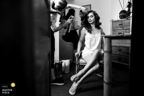 Wedding photojournalism at Bucharest - a vintage style photograph of a bride with her getting ready helpers fixing her hair
