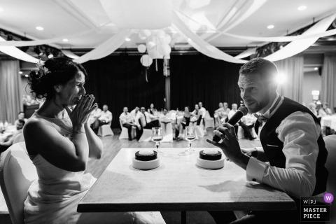 Pays de la Loire bruiloft fotojournalistiek beeld van een paar - bruidegom met een microfoon op een paar tafel