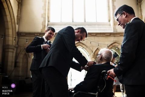 Dokumentarische Hochzeitsphotographie an der Surrey-Zeremonie des Mannes im Rollstuhl, der Hilfe mit Blumen erhält