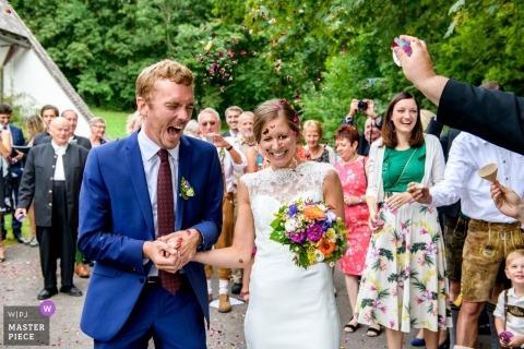 Hasenöhrl Hof Bayrischzell célébrant une cérémonie de mariage en plein air avec la mariée, le marié et des confettis.