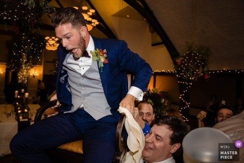 Boston documentary wedding photo - bar harbor club groom lifted in chair