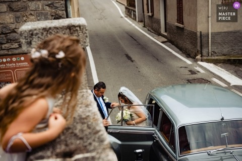 Italy wedding Image of a bride exiting a vintage limousine as seen from the perspective of a young flower girl on the second floor