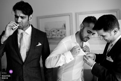 Hochzeitsfotos von Algarve, Portugal-Fotograf des rauchenden Bräutigams, während seine Trauzeugen die Knöpfe auf einem Hemd herausfinden