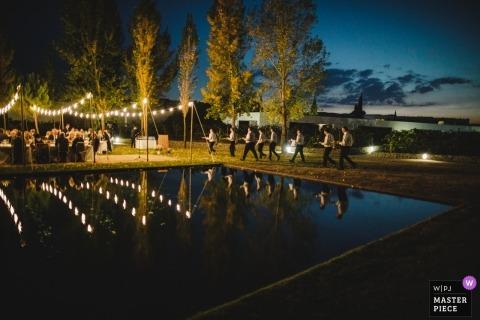 Photographie documentaire de mariage à Porto des vendeurs de services alimentaires apportant les repas aux invités à la réception en plein air au bord de la piscine