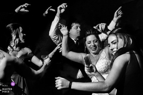 Wedding pictures of reception party guests dancing by Goiânia photographer