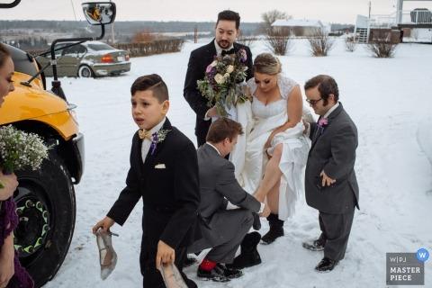Huwelijksshoot met Alberta-paar buiten in de sneeuw met schoolbus