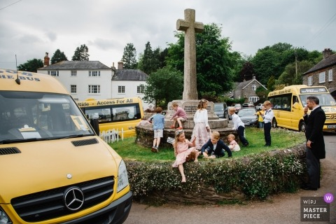 Wedding photojournalism at England reception with children and taxi shuttle vans outside