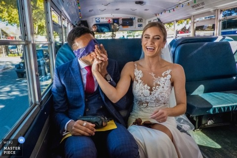 Solvang, Kalifornien-Hochzeitsfotojournalismusbild eines Paares, das den Bus reitet - küssende Hand, während die Augen verbunden werden