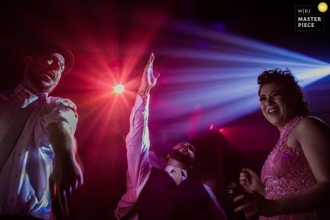 Rio Grande do Sul Hochzeit Fotojournalismus Bild von Gästen, die unter DJ-Beleuchtung tanzen