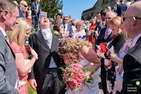 Wymeswold, Leicestershire, UK Hochzeitshooting mit einem Paar umgeben von Gästen unter Konfetti-Dusche