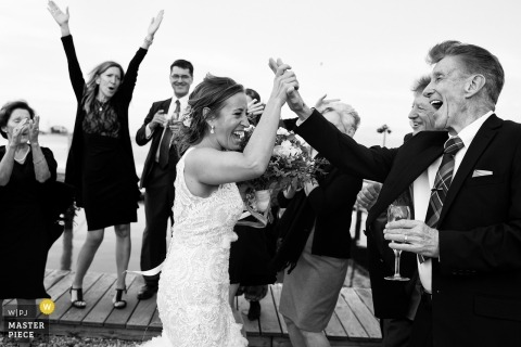 Nantucket, Massachusetts wedding shoot with a couple grasping hands during celebration moment with guests