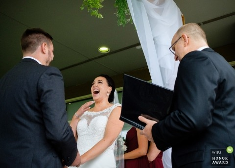 Picture of a couple laughing during ceremony by a top Toronto wedding photographer