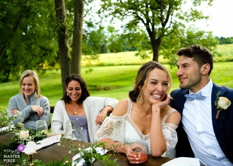 Toronto couple laughing at head table during their outdoor wedding reception