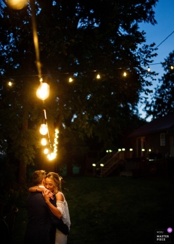 Wedding shoot at reception outdoors with Toronto couple dancing under strings of lights
