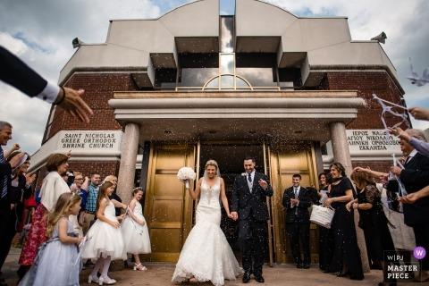 Queens, die Fotojournalismusbild eines Paares heiraten, das die Zeremoniehalle mit ihren Gästen und Familie beenden, die sie an zujubeln