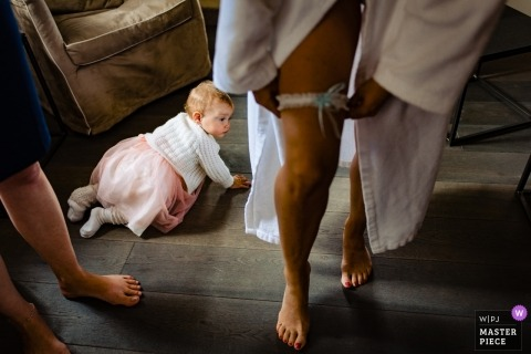 Wedding photojournalism at Hesse with baby girl in dress crawling on the floor by the bride